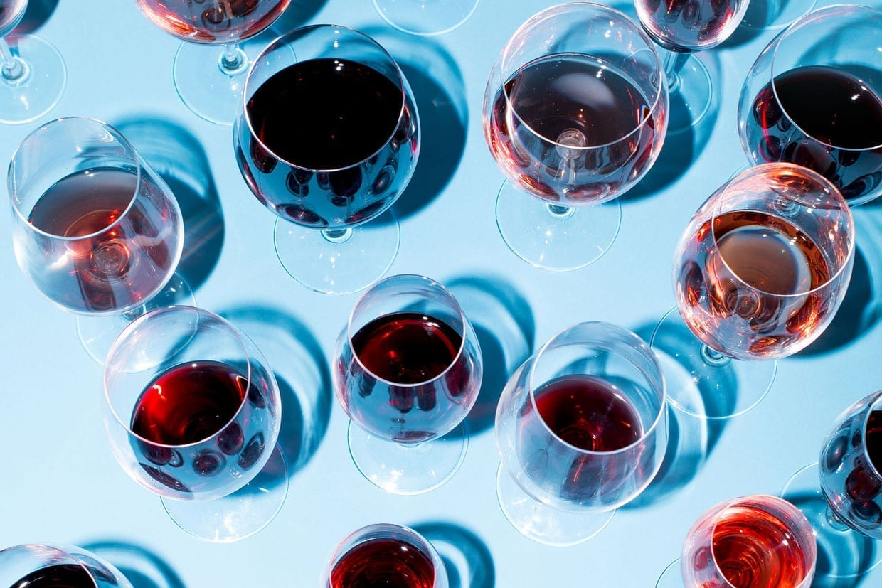 A photo of different wine glasses on a blue background.