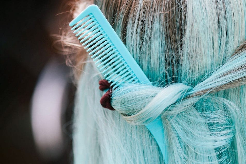 A woman with blue hair with comb stuck in it.