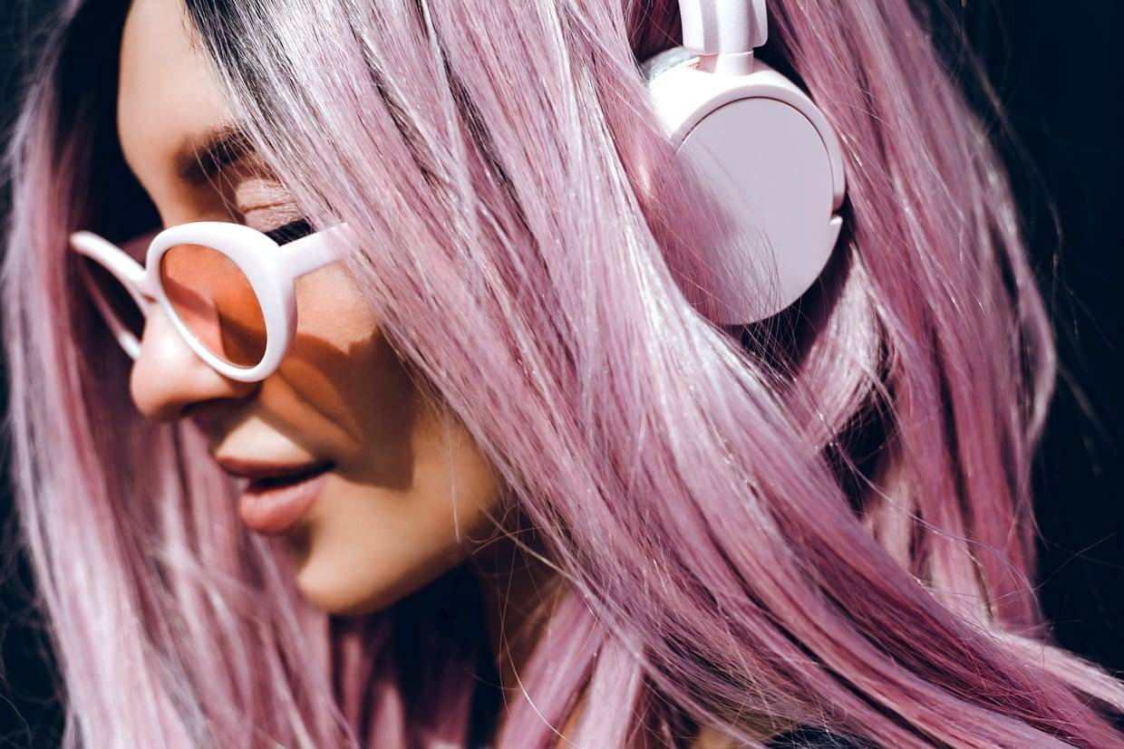 A woman with purple pink hair listening to podcasts on headphones.