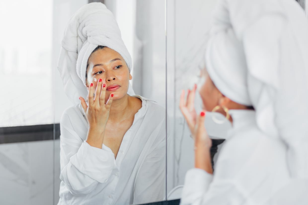 A woman applying cream on her face in front of a mirror.