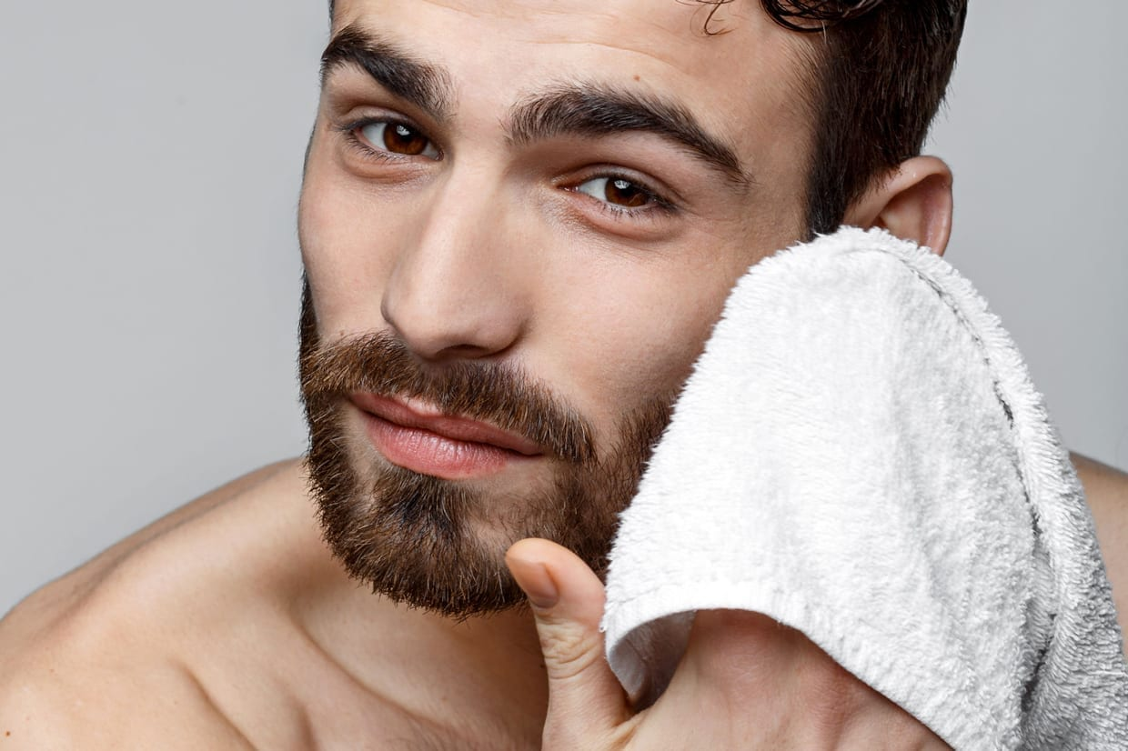 A man wipes his face with a towel.