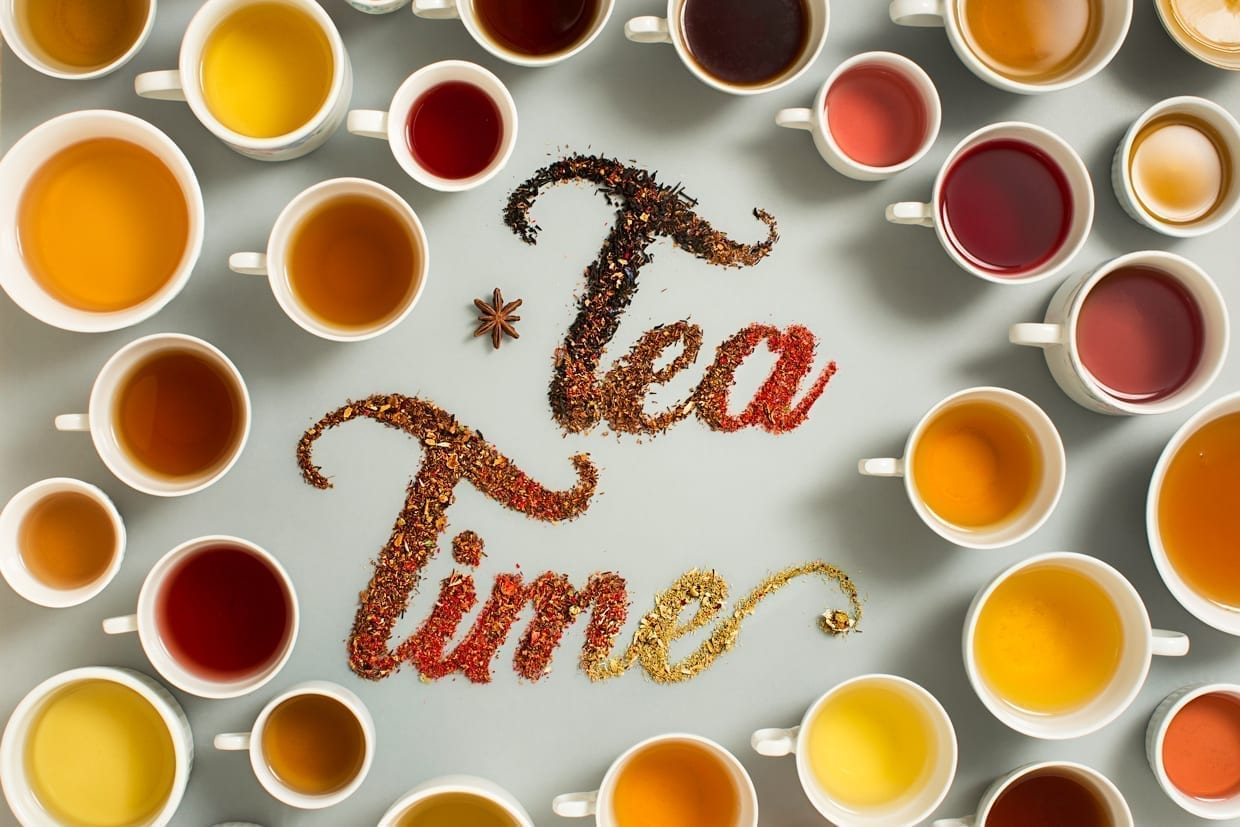 Overhead shot of the words, Tea Time, written with dry tea leaves and surrounded by cups filled with multicolor teas.