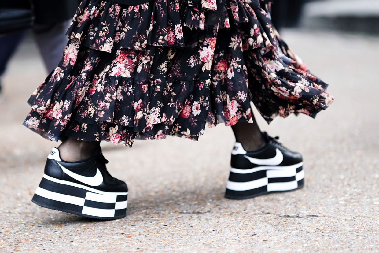 A person in a floral print ruffled dress and Nike black and white platform sneakers in London, Jan. 6, 2019.