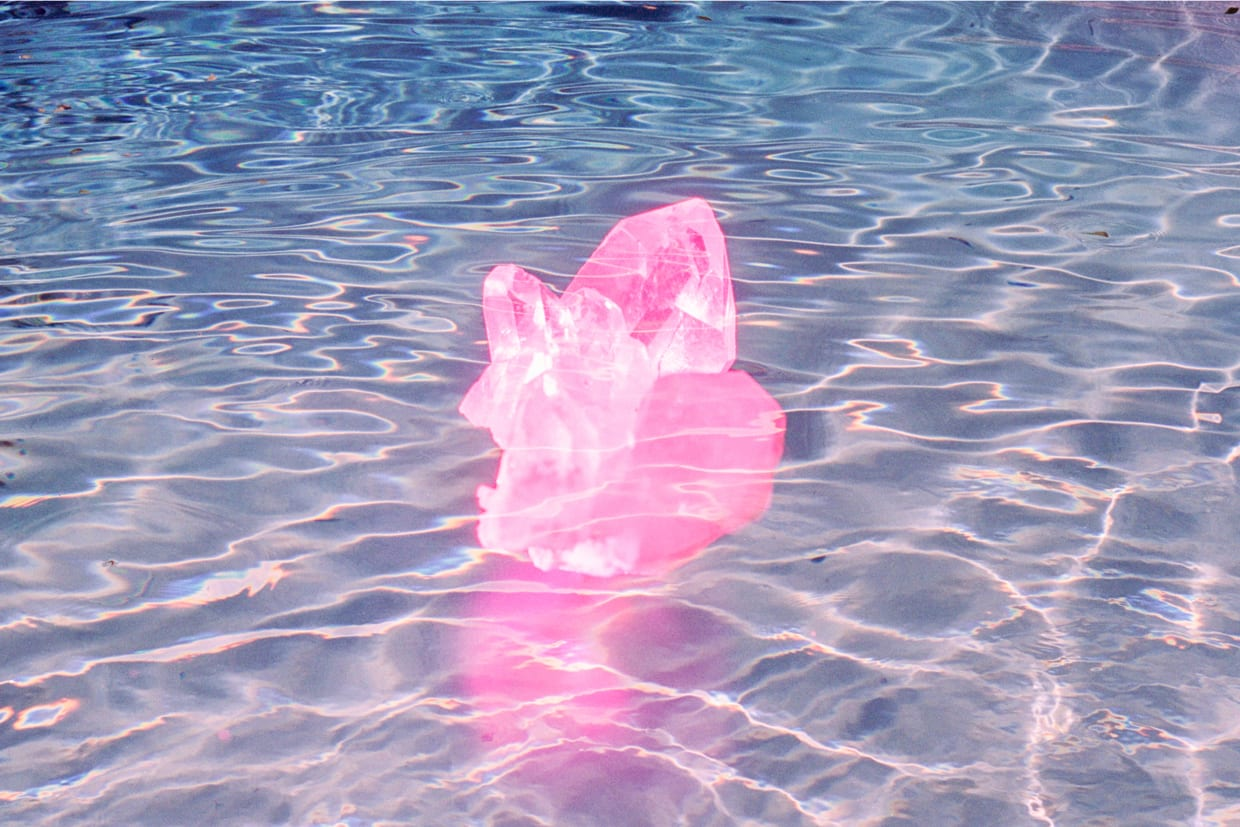 Pink crystal floating on blue pool of water.