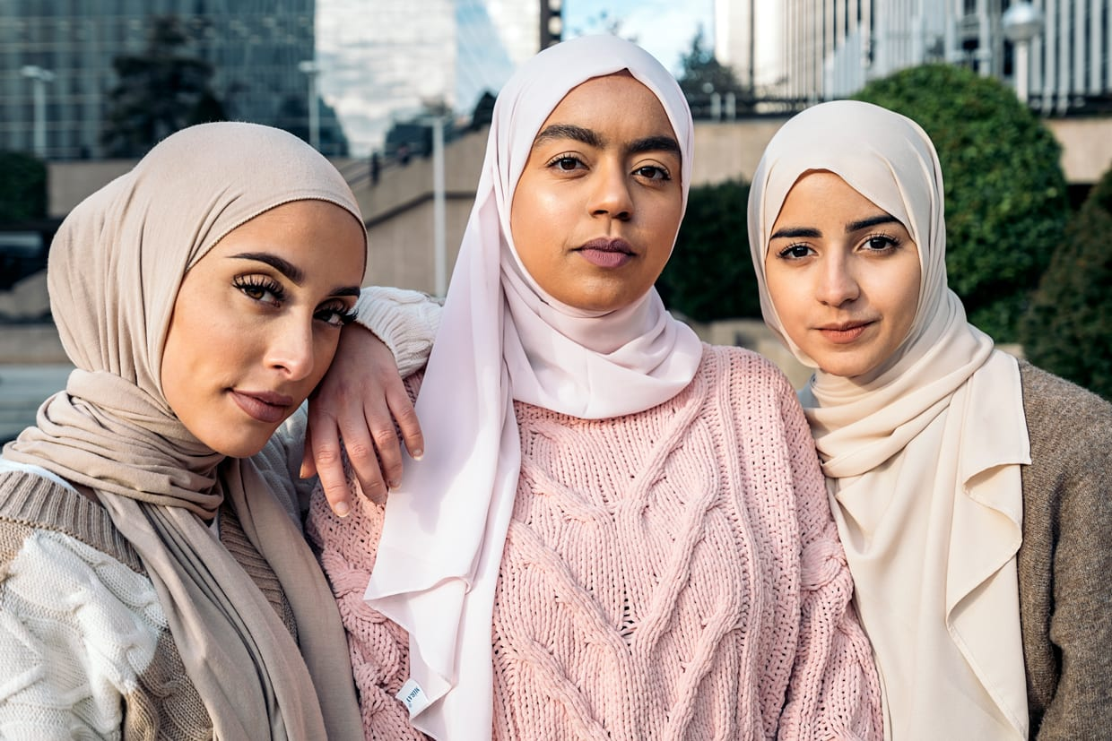 Three young Muslim women wearing hijabs and looking at the camera.